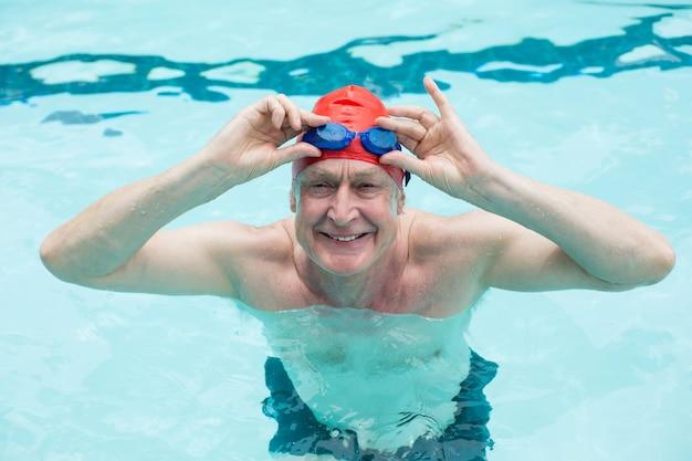 Vue grand angle de l'homme senior tenant des lunettes dans la piscine