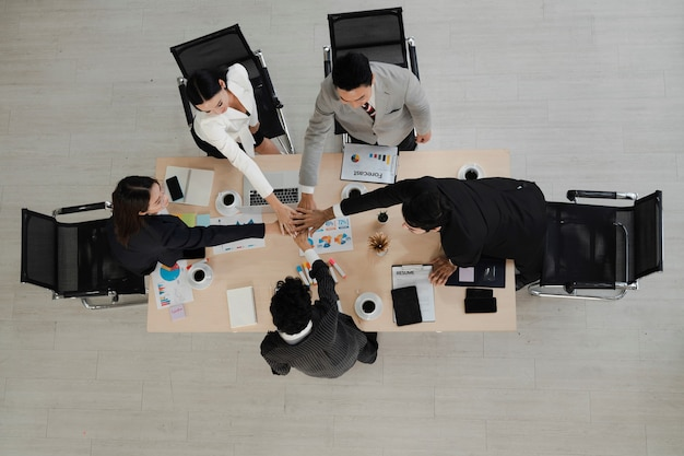 Vue en grand angle des hommes d'affaires empilent leurs mains ensemble en cercle sur le bureau lors d'une réunion au bureau, montre ensemble, concept d'union, équipe réussie