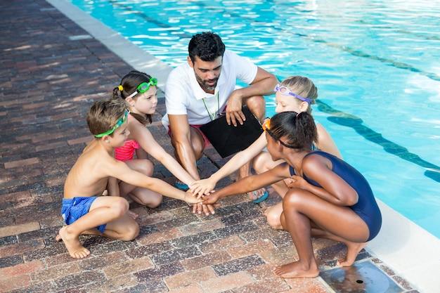 Vue grand angle de l'instructeur et des enfants empiler les mains au bord de la piscine