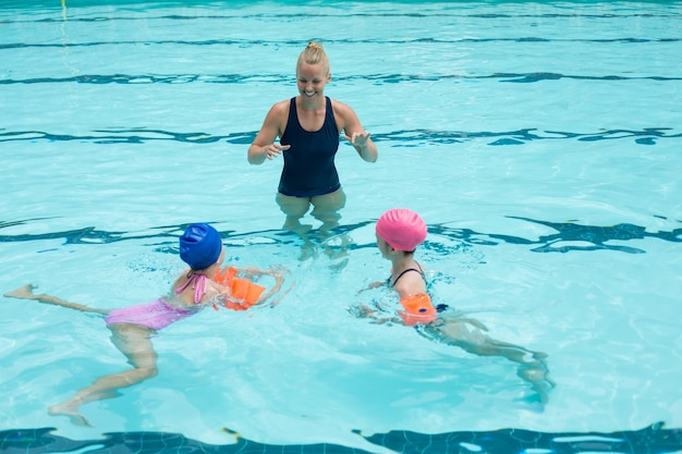 Vue grand angle de l'instructeur heureux d'aider les enfants dans la piscine