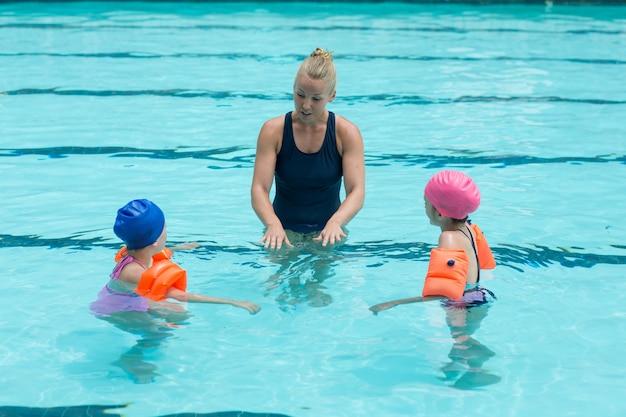 Vue grand angle de l'instructrice aidant les enfants dans la piscine