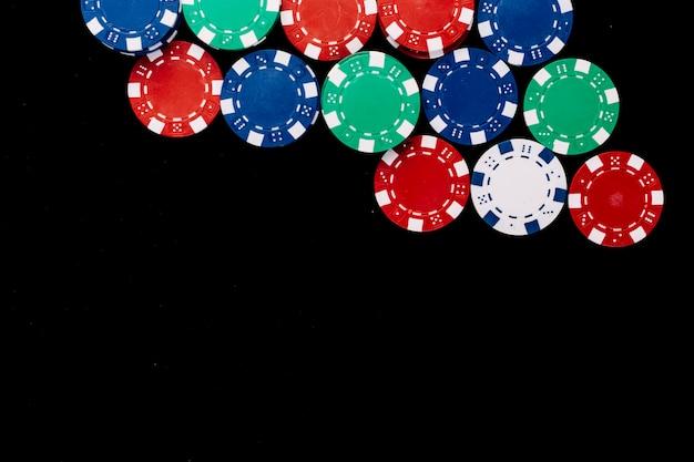Vue grand angle de jetons de poker colorés sur fond noir