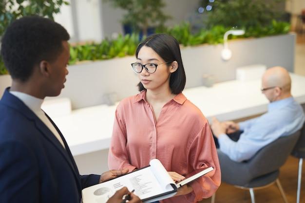 Vue grand angle à la jeune femme d'affaires asiatique parler à un partenaire tout en discutant de projet dans un bureau moderne