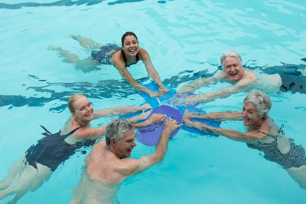 Vue grand angle de joyeux formateurs et nageurs seniors dans la piscine