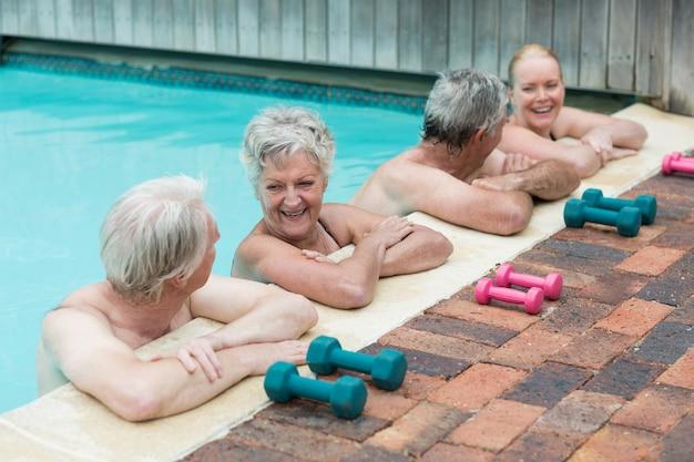 Vue grand angle de joyeux nageurs s'appuyant sur la piscine