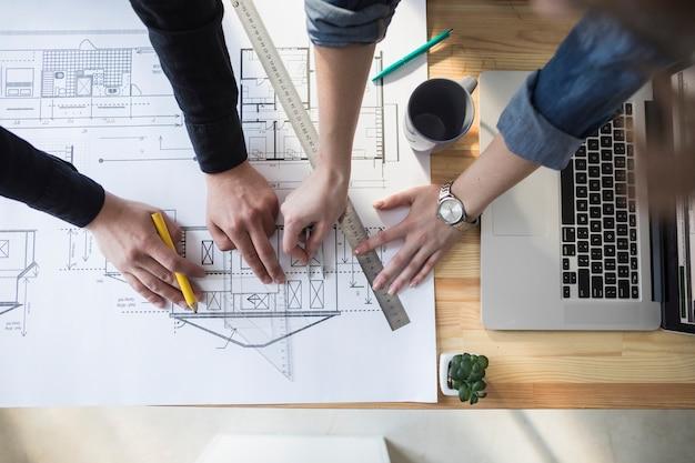 Vue grand angle de la main du travailleur travaillant sur blueprint au-dessus d'une table en bois sur le lieu de travail
