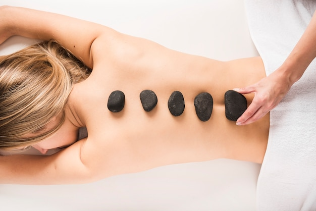 Vue grand angle d'une main de thérapeute plaçant une pierre chaude sur le dos de la femme