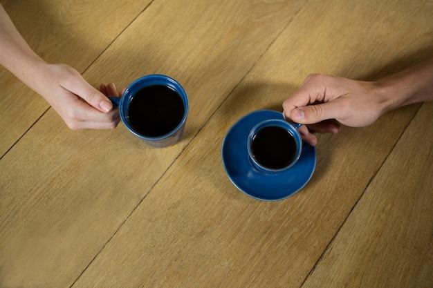 Vue grand angle des mains de couple tenant des tasses à café au café