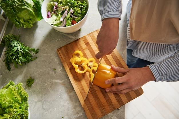 Vue grand angle des mains féminines tenant un couteau et coupant le poivron jaune en anneaux. fermer.
