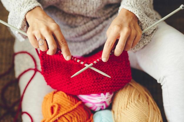 Vue grand angle des mains d'une femme faisant du tricot avec une aiguille, assise sur le sol dans le salon à la maison. bouchent les mains de la femme avec une aiguille à tricoter et font un travail de tricot.