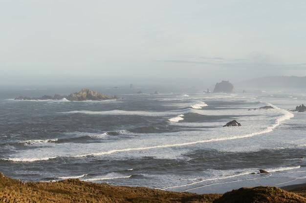 Vue grand angle de la mer ondulée entourée de rochers couverts de brouillard pendant la journée