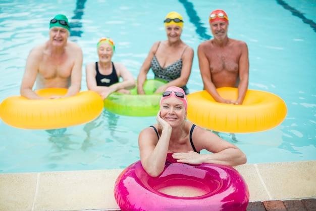 Vue grand angle des nageurs avec anneaux gonflables dans la piscine