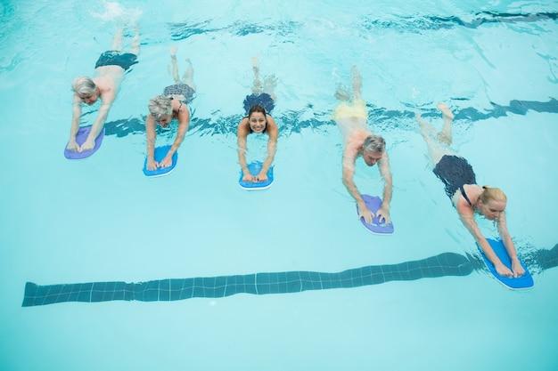 Vue grand angle des nageurs seniors et formateur nageant avec des planches dans la piscine