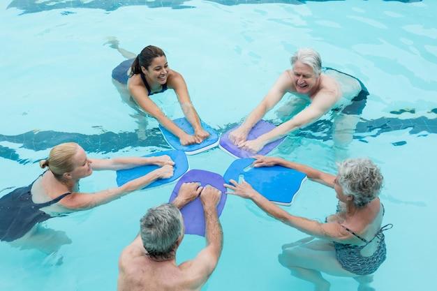 Vue grand angle des nageurs seniors avec formateur profitant de la piscine