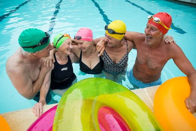 Vue grand angle des nageurs seniors heureux bénéficiant de la piscine