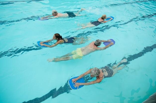 Vue grand angle des nageurs seniors avec instructeur de natation dans la piscine