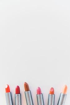 Vue grand angle de nuances de rouge à lèvres sur fond blanc disposées dans une rangée