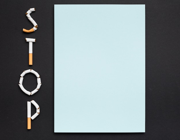 Vue grand angle de papier blanc avec texte stop fabriqué à partir de cigarettes