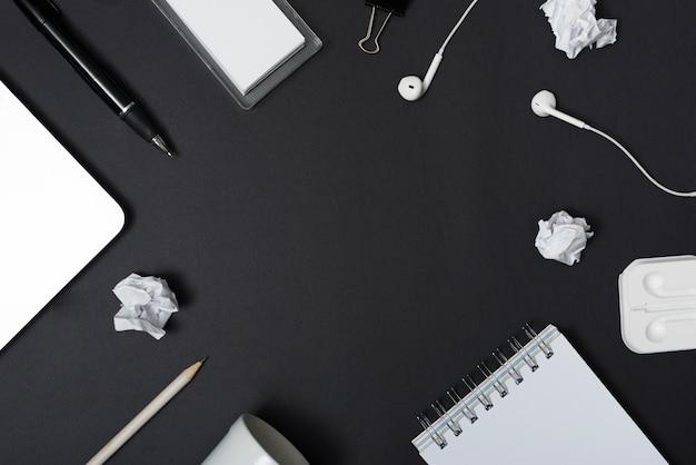 Vue grand angle de papier froissé avec papeterie sur fond noir