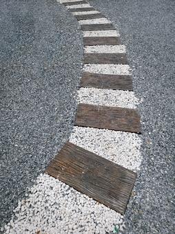 Vue grand angle d'une passerelle incurvée à l'aide de blocs de bois et de petites pierres de gravier
