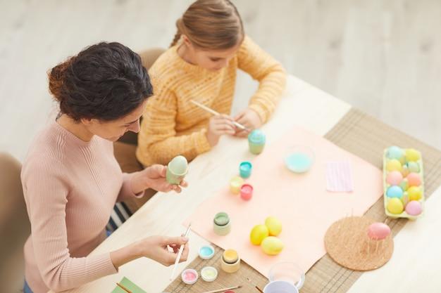 Vue grand angle à la peinture de la mère et de la fille des oeufs de pâques aux couleurs pastel assis à table dans un intérieur de cuisine confortable, espace copie