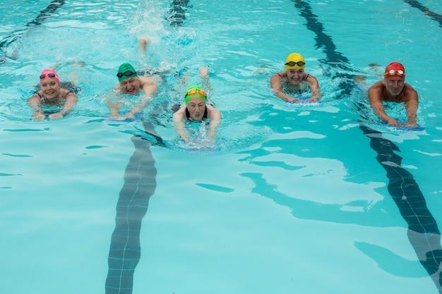 Vue grand angle de personnes avec des planches de natation dans la piscine