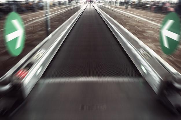 Vue grand angle en perspective d'un escalator commercial à grande vitesse illuminé et spacieux, moderne et bleu clair, avec une piste floue rapide de main courante dans un mouvement de circulation en voie de disparition dans le couloir de l'aéroport.