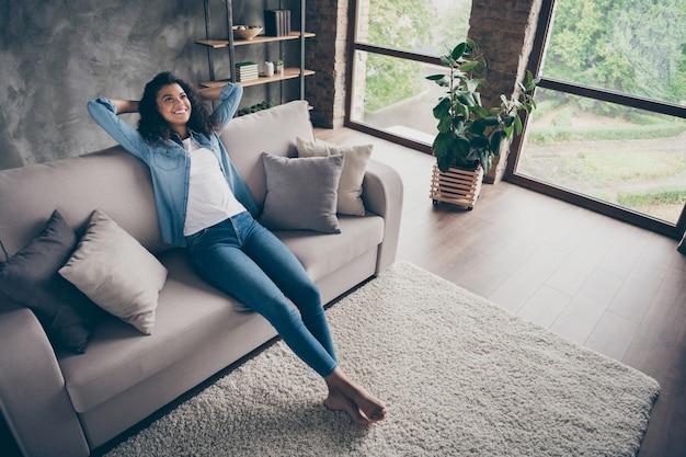 Vue grand angle photo de belle dame à la peau foncée tenir la main derrière la tête profiter du week-end après la réparation à plat à la recherche de rêve assis canapé confortable tenue décontractée salon à l'intérieur