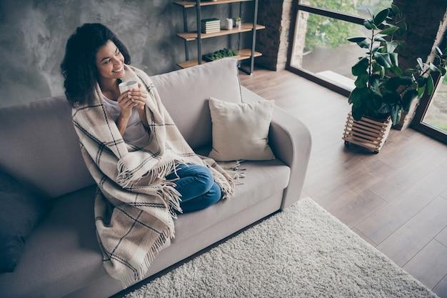 Vue grand angle photo de belle dame peau foncée tenir tasse de boisson de café chaud profiter du week-end à la maison s'asseoir confortable canapé tenue décontractée recouverte d'une couverture salon à l'intérieur