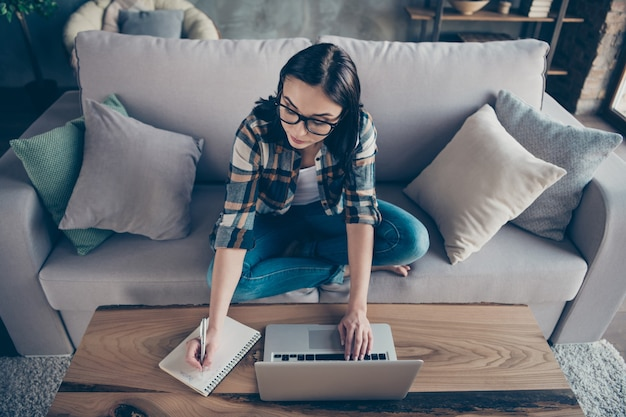Vue grand angle photo de jolie femme d'affaires textos cahier collègues travaillant à la maison en remarquant les détails de démarrage dans l'organisateur porter des vêtements décontractés s'asseoir canapé à l'intérieur