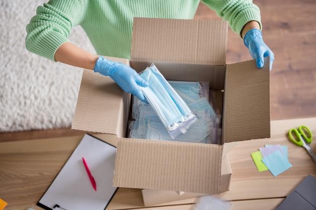 Vue grand angle photo recadrée d'une femme d'affaires organiser des masques médicaux pour le visage grande boîte livraison gratuite vérifier respirateurs de sécurité antiviraux sac à fermeture éclair envoyer le colis au bureau à domicile du client à l'intérieur