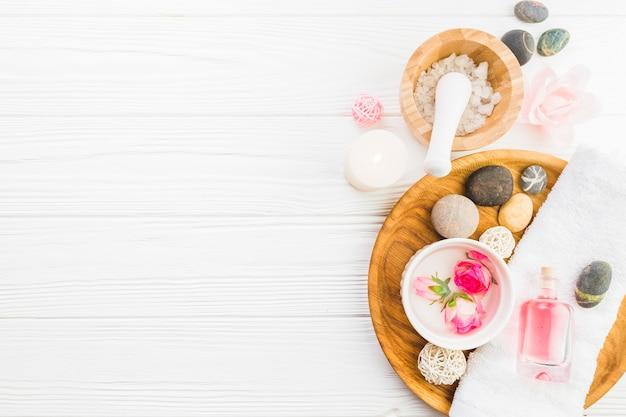 Vue grand angle sur les pierres du spa; serviette; fleurs et huile sur fond blanc