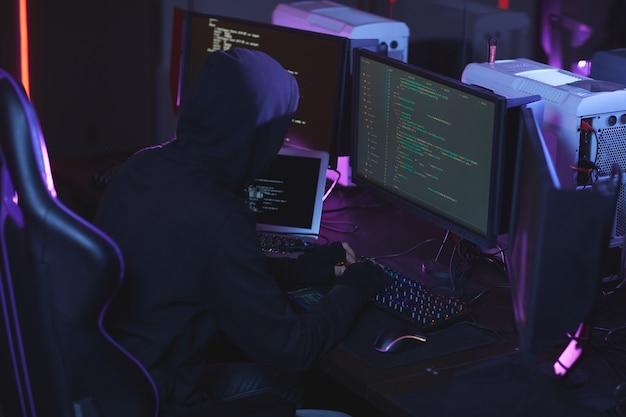 Vue grand angle à un pirate informatique méconnaissable portant une cagoule tout en travaillant sur le code de programmation dans une pièce sombre, copiez l'espace