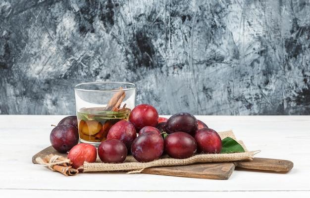 Vue grand angle des prunes et de l'eau de désintoxication sur une planche à découper avec des feuilles et un morceau de sac sur une planche de bois et une surface en marbre bleu foncé. horizontal