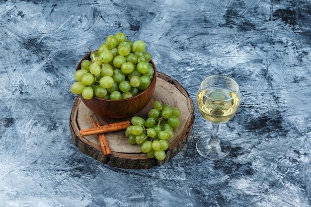 Vue grand angle de raisins blancs, cannelle sur planche de bois avec verre de whisky sur fond de marbre bleu foncé. horizontal