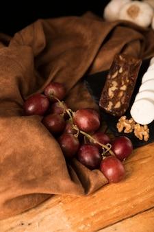 Vue grand angle de raisins rouges biologiques sur un drap marron sur une table en bois