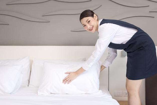 Vue grand angle d'une serveuse faisant le lit, femme de ménage nettoyant une chambre d'hôtel