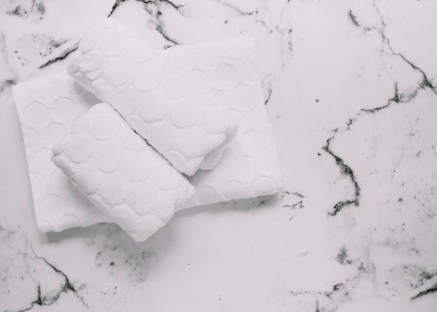 Vue grand angle de serviettes blanches sur fond de marbre