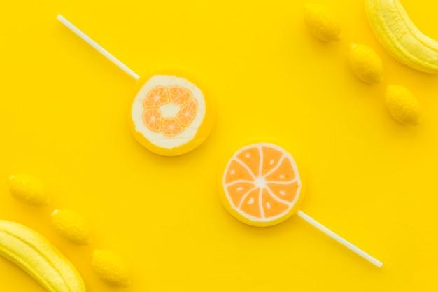 Vue grand angle de sucettes d'agrumes; bonbons à la banane et au citron sur fond jaune