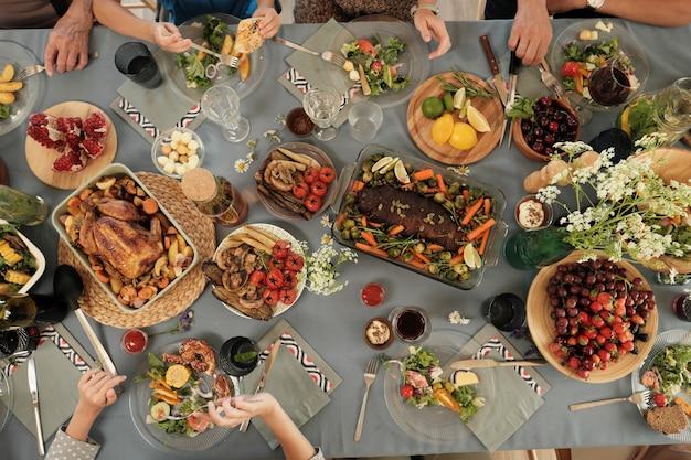 Vue grand angle de la table de fête avec différents plats délicieux avec des gens assis et mangeant