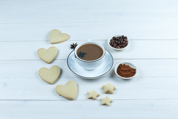 Vue grand angle tasse de café avec des biscuits, des grains de café et du café instantané sur fond de planche de bois blanc. horizontal
