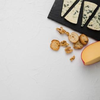 Vue grand angle de la tranche de pain et des morceaux de fromage avec noix