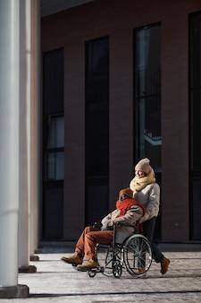 Vue grand angle vertical sur un homme afro-américain en fauteuil roulant se déplaçant dans une ville urbaine éclairée par la lumière du soleil avec une femme aidant, espace pour copie