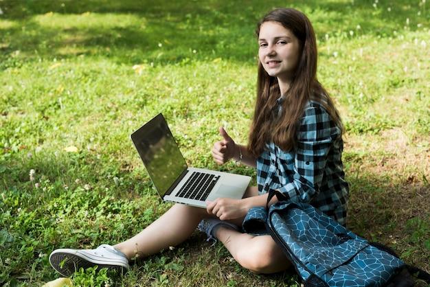 Vue grand angle vue de côté d'une écolière à l'aide d'un ordinateur portable