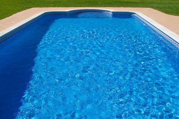 Vue d'une grande piscine de luxe avec de l'herbe.