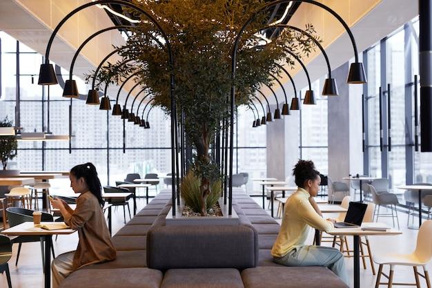 Vue graphique grand angle sur deux jeunes femmes assises à des tables dans un café des côtés opposés avec distanciation sociale, espace de copie