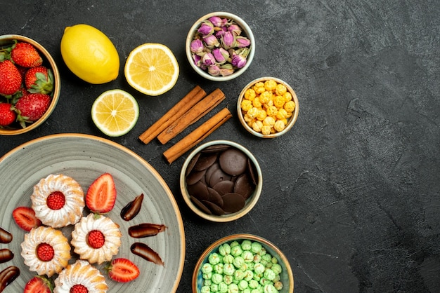 Vue en gros plan des biscuits au chocolat et aux fraises différents bonbons au thé noir citrons noisettes bols de chocolat sur le côté gauche de la table