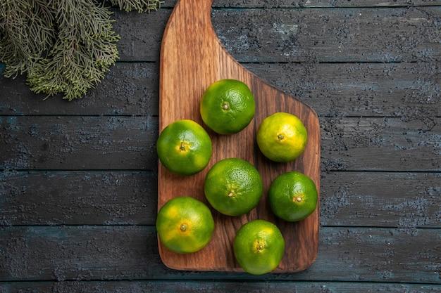 Vue en gros plan des citrons verts et des branches des citrons verts sur la planche de cuisine à côté des branches d'arbres