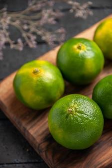 Vue en gros plan des citrons verts sur la table des citrons verts à bord sur la planche à découper à côté des branches d'arbres