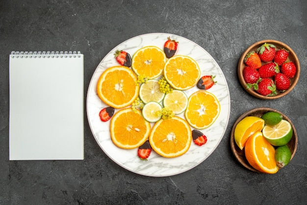 Vue en gros plan des fruits sur une assiette de table de fraises et de citron recouverts de chocolat orange entre des bols d'agrumes et de baies et un cahier blanc
